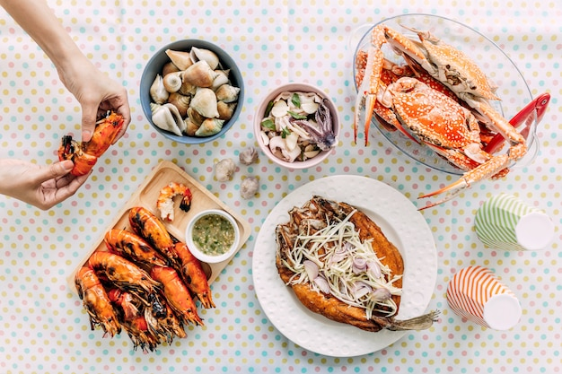 Top view of thai seafoods are grilled prawns (shrimps) in the shell, steamed crabs, grilled laevistrombus canarium, grilled squid and deep fried sea bass with sweet fish sauce and mango salad.