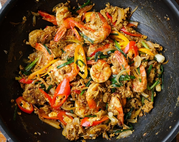 Top view of thai stir fried shrimps with yellow curry powder in a pan
