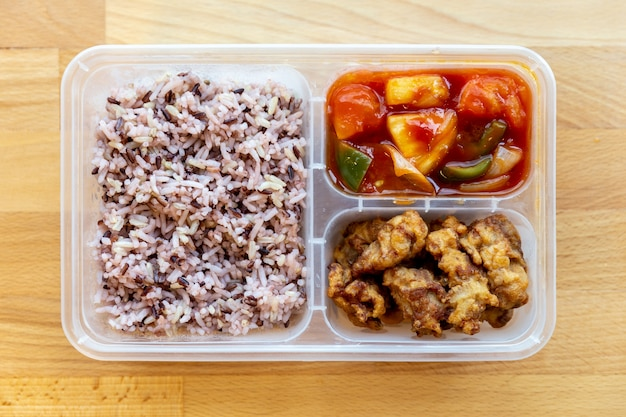 Top view of thai styled organic sweet and sour fried with pork and rice berry in food grade box.