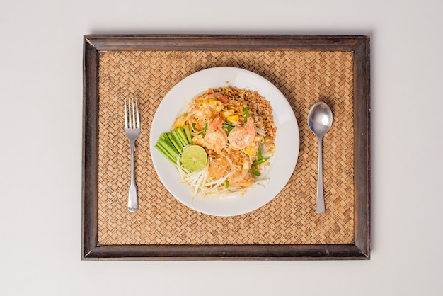 Top view of thai traditional food  pad thai noodles with shrimp in dish on wooden table