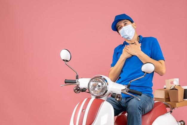 Vista dall'alto di un corriere grato in maschera medica che indossa un cappello seduto su uno scooter su una pesca pastello