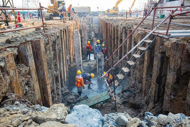 맨 위 보기 남성 작업자는 좁은 공간 내부에 굴착기로 파고 있는 구멍에 석고 기계 콘크리트를 사용했습니다. 주위에 흙이 있었습니다.