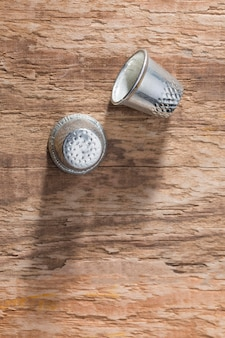 Top view of thimbles on wooden surface