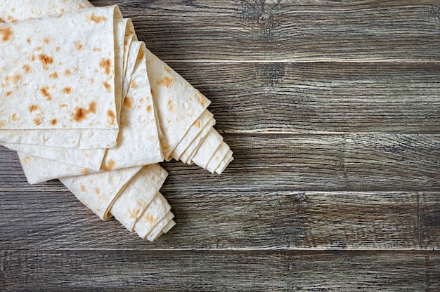Top view thin pita bread on wooden background.
