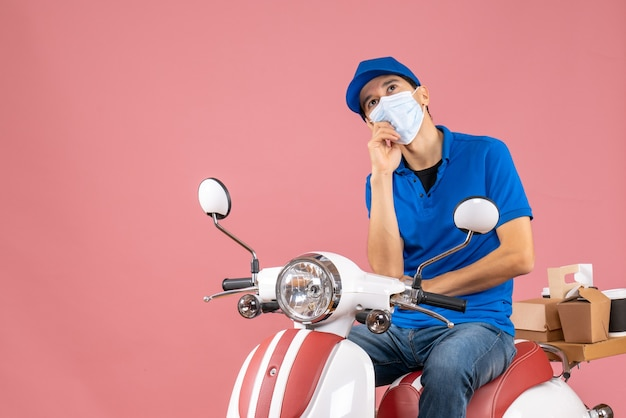 Vista dall'alto del corriere pensante in maschera medica che indossa un cappello seduto su uno scooter che consegna ordini su pesca pastello
