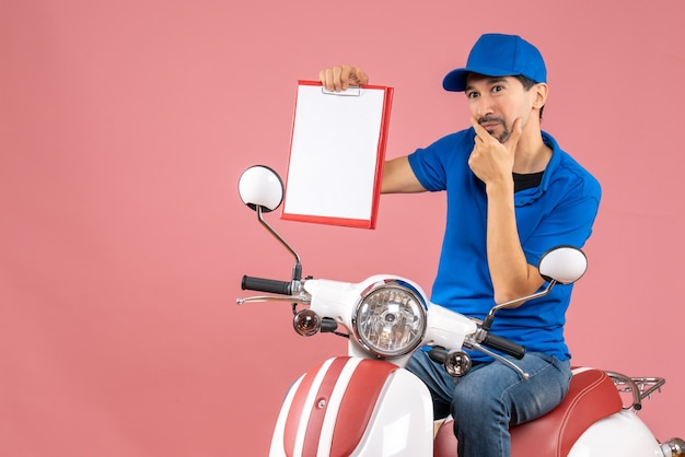 Top view of thinking courier man wearing hat sitting on scooter holding document on pastel peach