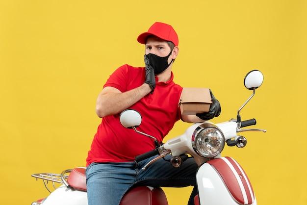 Vista dall'alto di pensare corriere uomo che indossa camicetta rossa e guanti cappello in maschera medica seduto su scooter tenendo l'ordine