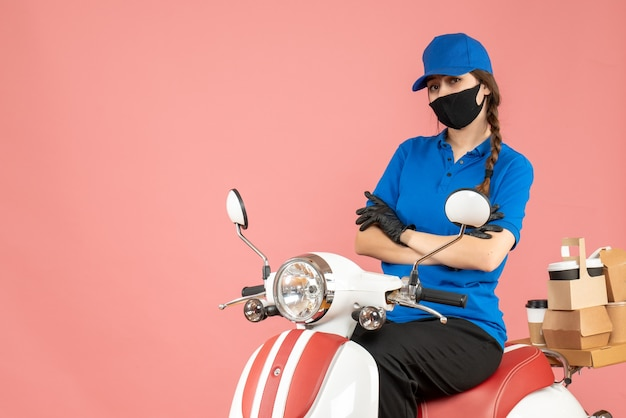 Top view of thinking courier woman wearing medical mask and gloves sitting on scooter delivering orders on pastel peach