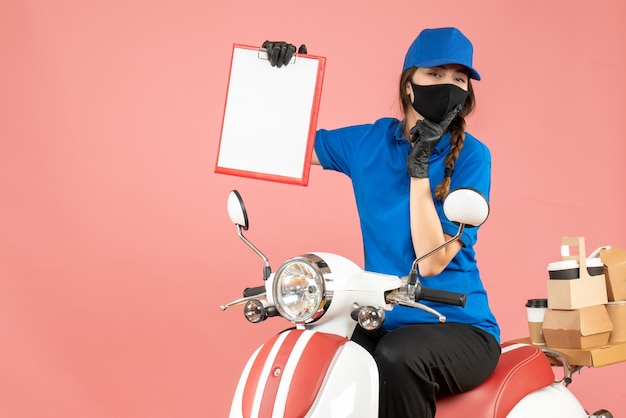 Top view of thinking courier woman wearing medical mask and gloves sitting on scooter holding empty paper sheets delivering orders on pastel peach