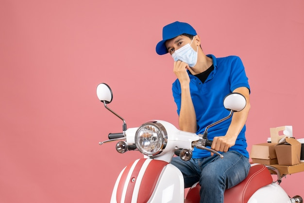 Top view of thinking delivery guy in medical mask wearing hat sitting on scooter on pastel peach