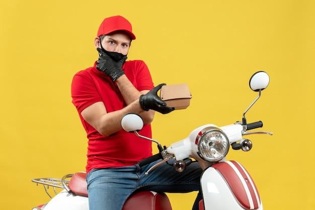 Vista dall'alto del ragazzo delle consegne di pensiero che indossa guanti di camicetta e cappello rossi in mascherina medica che si siede sullo scooter che mostra l'ordine