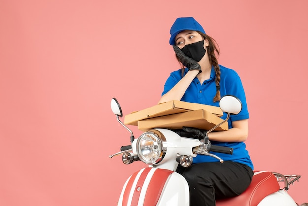 Vista dall'alto del corriere femminile pensante che indossa maschera medica e guanti seduto su uno scooter che consegna ordini su pesca pastello