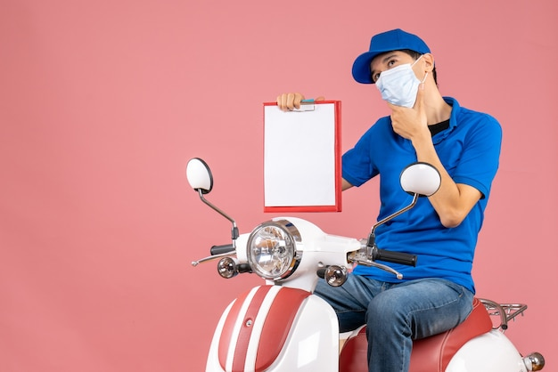 Top view of thinking male delivery person in mask wearing hat sitting on scooter showing document on pastel peach