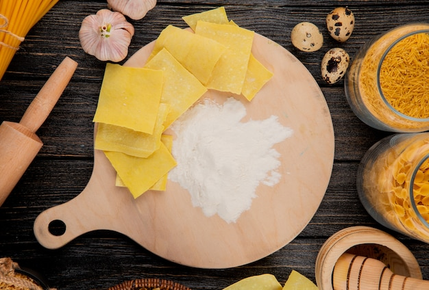 Top view of thinly rolled raw dough cut into squares on wooden board with flour and different types of italian raw pasta in glass jars on black wooden background