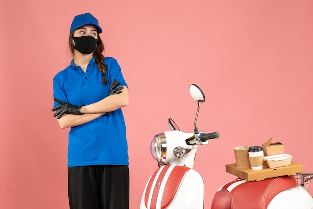 Vista dall'alto della premurosa ragazza del corriere in maschera medica in piedi accanto alla moto con una torta di caffè su di essa su color pesca pastello