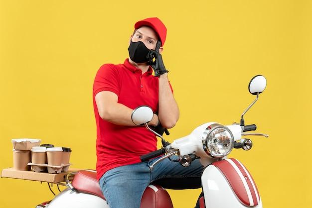 Vista superiore del giovane adulto premuroso che indossa la camicetta rossa e guanti del cappello nella mascherina medica che trasporta l'ordine che si siede sullo scooter sulla parete gialla