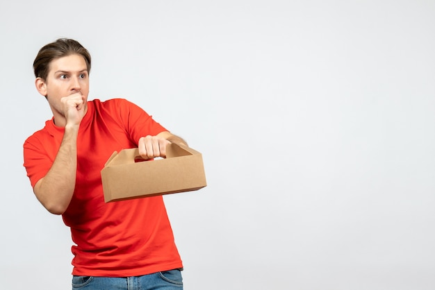 Vista dall'alto del giovane premuroso in camicetta rossa che tiene la scatola sul muro bianco