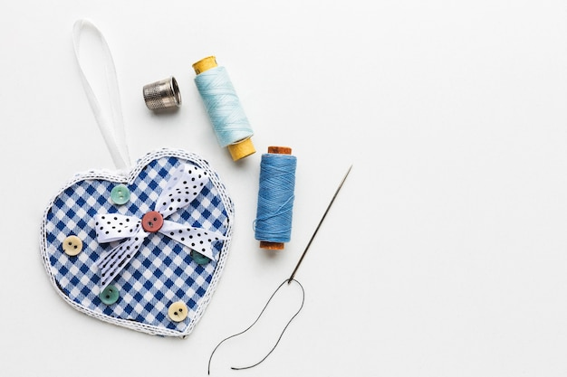 Top view of thread with needles and heart shaped fabric