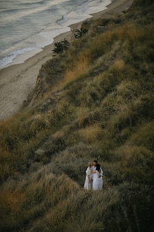 Vista dall'alto di tre persone adulte che si abbracciano insieme sulla collina erbosa