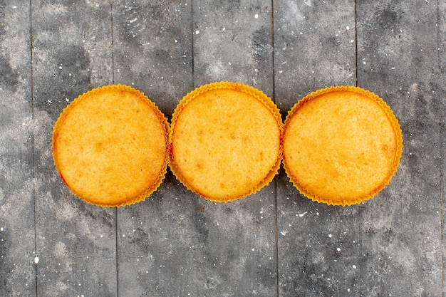 Top view three cakes brown cooked round on the grey rustic wooden background
