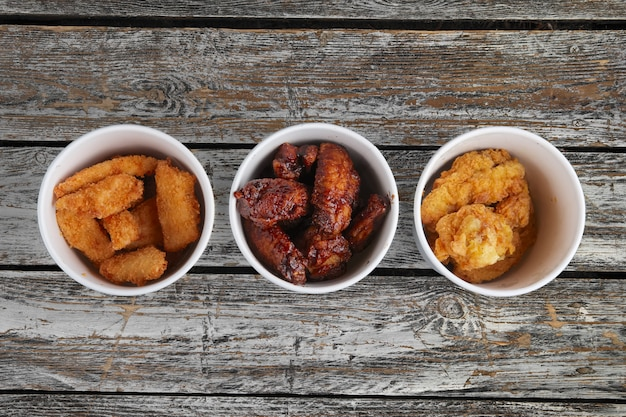 Top view of three cardboard containters with fried chicken wings on wooden table
