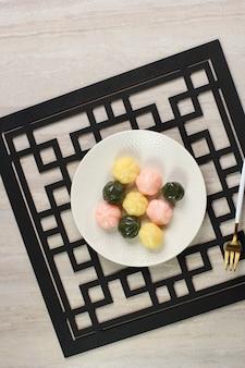 Top view 삼색 꿀떡은 공 모양의 떡으로 꿀과 참깨를 채운 한국의 추석 전통 과자입니다. 하얀 접시에 제공