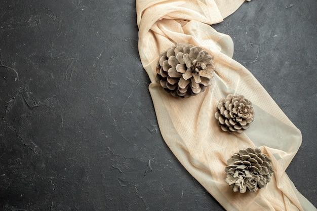 Vista dall'alto di tre coni di conifere su un asciugamano di colore nudo su sfondo di colore nero