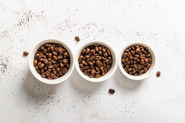 Top view of three cups with roasted coffee beans