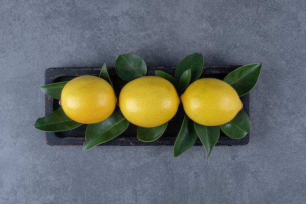 Top view of three fresh lemon with leaves on grey background.