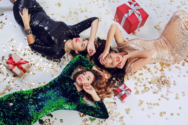 Top view on three gorgeous girls lying on the floor, celebrating new year or birthday party. wearing luxury sequins dress  and jewelry. golden shining confetti , red gift boxes.