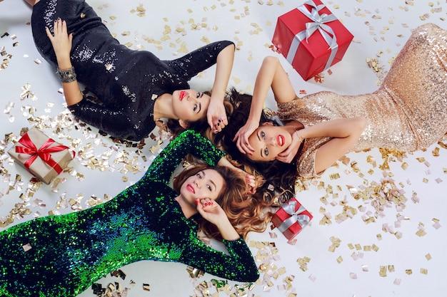 Vista dall'alto su tre bellissime ragazze sdraiate sul pavimento, che celebrano il capodanno o la festa di compleanno. indossare abiti e gioielli di paillettes di lusso. coriandoli splendenti dorati, scatole regalo rosse.