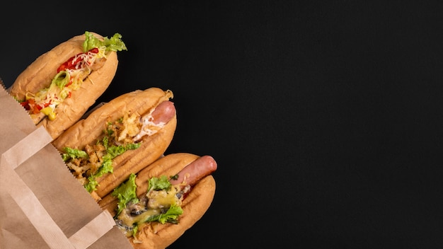 Top view of three hot dogs in paper bag with copy space