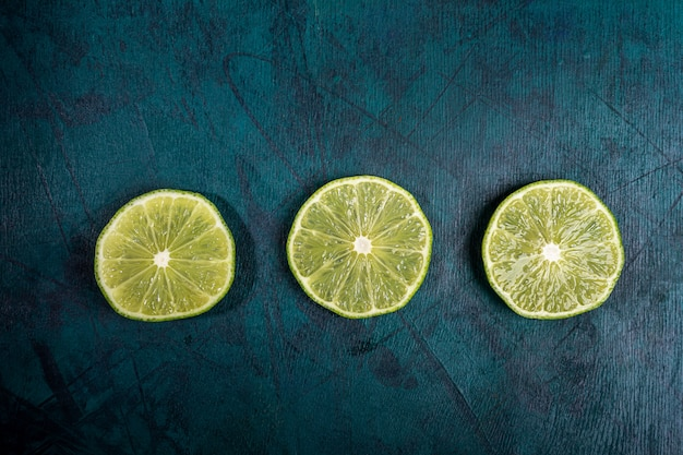 Top view of three juicy lime slices  laid out in row on emerald background.