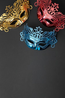 Top view of three masks for carnival with copy space