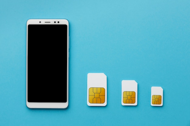 Top view of three sim cards with smartphone and copy space