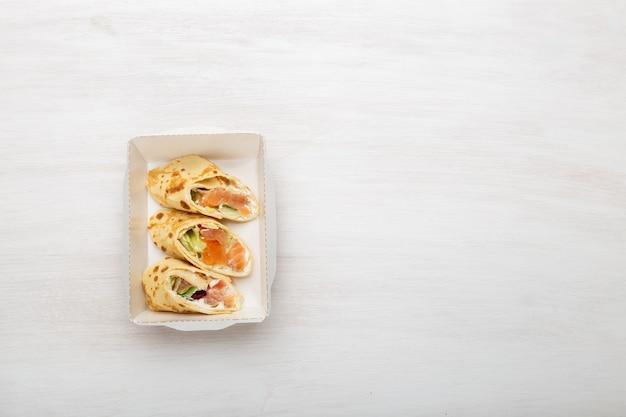 상위 뷰 빨간 물고기와 채소와 치즈가 들어간 팬케이크 세 조각이 채소와 채소 옆에있는 흰색 테이블에있는 도시락에 놓여 있습니다. 적절한 영양의 개념. 공간 복사