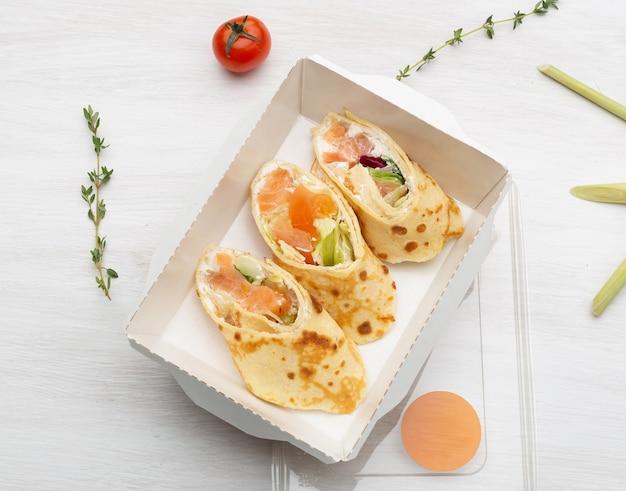 Вид сверху: три ломтика блинов с красной рыбой, зеленью и сыром лежат в ланч-боксе на белом столе рядом с зеленью и овощами. понятие о правильном питании.