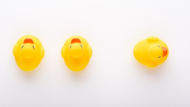 Top view three toy yellow ducklings on white background, creative concept