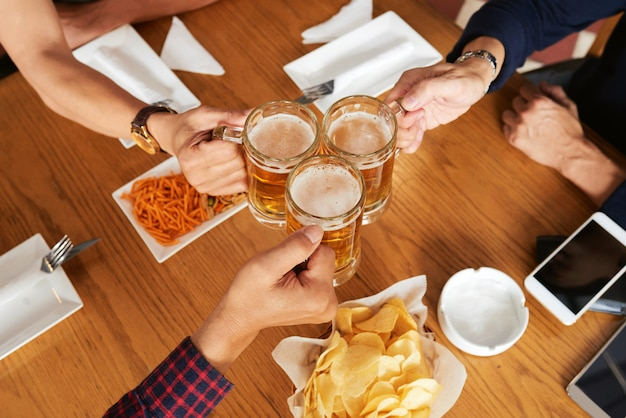 Top view of three unrecognizable friends toasting with beer mugs