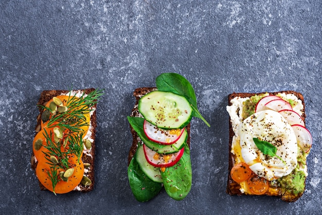 Top view three vegetarian toasts with poached eggs, cottage cheese, yellow tomatoes, radish, cucumber, spinach on grey background