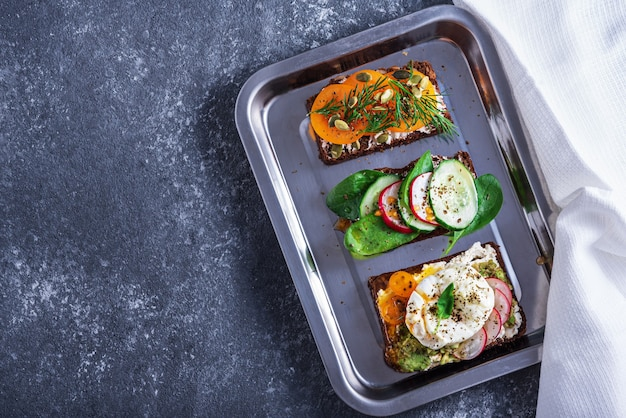 Top view three vegetarian toasts with poached eggs, cottage cheese, yellow tomatoes, radish, cucumber, spinach on tray on grey background, healthy snack concept