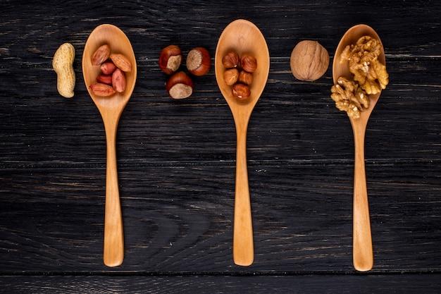 Вид сверху три деревянные ложки с фундуком и орехами очищенные и в скорлупе