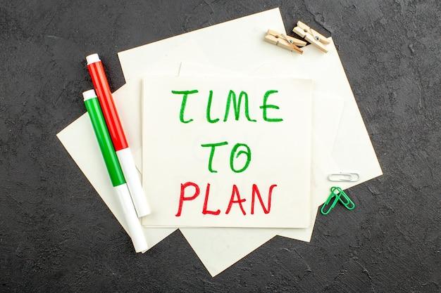 ノート紙の洗濯ばさみに書かれた計画の上面図時間黒の赤と緑のマーカーの宝石クリップ