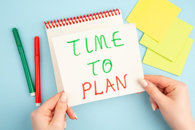 女性の手の付箋に書かれた計画のトップビュー時間赤と青の緑のマーカー