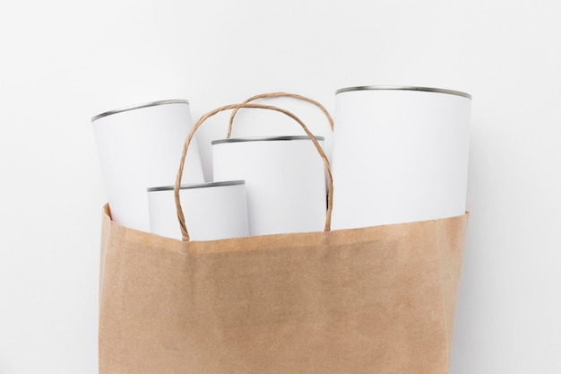 Top view of tin cans with blank labels in paper bag