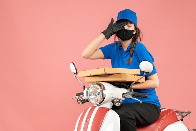 Vista dall'alto del corriere femminile stanco che indossa maschera medica e guanti seduto su uno scooter che consegna ordini su pesca pastello