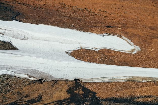 Вид сверху на красивый небольшой ледник, талую воду и мхи на каменистой горной стороне