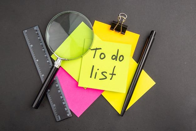 노란색 스티커 메모에 쓰여진 목록을 수행하는 상위 뷰 어두운 색의 스티커 메모 루파 펜 눈금자