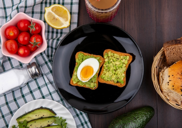 Top view of toast bread slices with avocado pulps and egg on a black plate with tomatoes lemon on checked tablecloth and wooden surface