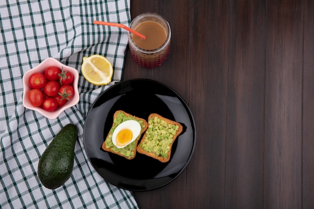 Top view of toast bread with avocado pulps and egg with tomatoes on a pink bowl lemon avocado on checked tablecloth and wooden surface